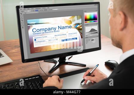 Designer Making Webpage Design On Computer Using Graphic Tablet - Stock Photo