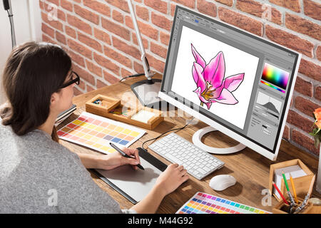 High angle view of female designer drawing flower on computer using graphic tablet in office - Stock Photo
