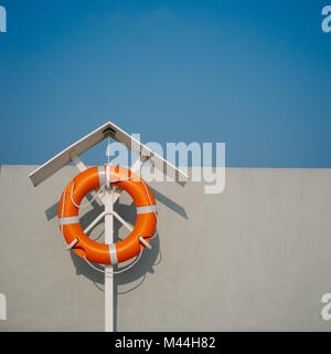 Orange life buoy on the pier - Stock Photo