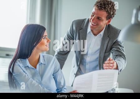 Happy young businesspeople discussing over document in office - Stock Photo