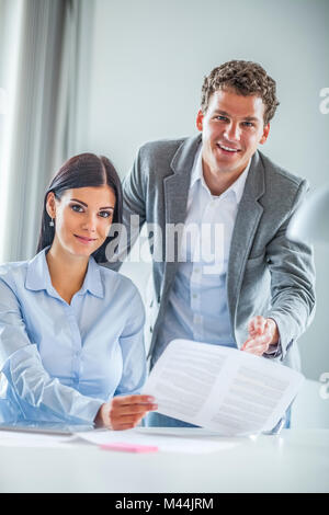 Portrait of happy young businesspeople discussing over document in office - Stock Photo