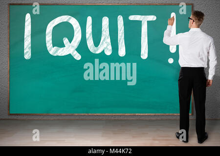 Full length rear view of businessman writing I Quit on blackboard - Stock Photo