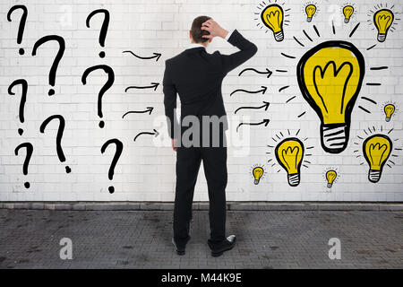 Rear view of confused businessman looking at question marks and light bulbs on wall - Stock Photo