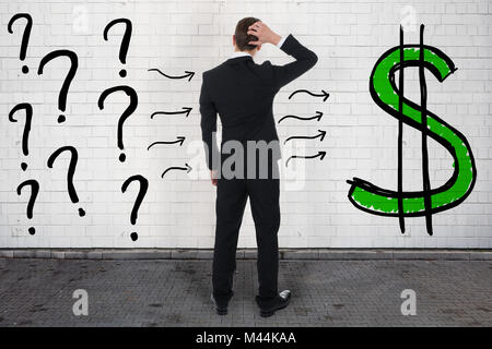 Rear view of confused businessman looking at question marks and dollar sign on wall - Stock Photo