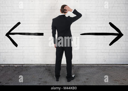 Full length rear view of confused businessman looking at opposite arrow signs on wall - Stock Photo