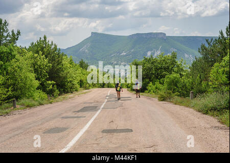 Two hiking people on the road - Stock Photo