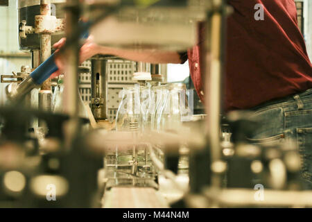 A mature adult man is operating an old fashioned automatic milk bottling machine in small ecological dairy farm. - Stock Photo