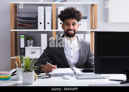 Portrait Of A Young Happy Businessman Working In Office - Stock Photo