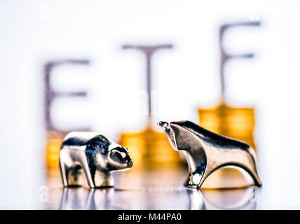Bull and bear with stacks of coins and the letters ETF in the background - Stock Photo