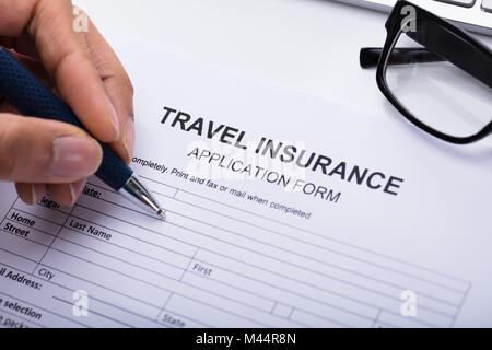 Close-up Of A Person's Hand Filling Travel Insurance Form - Stock Photo
