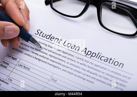 Close-up Of A Person's Hand Filling Student Loan Application Form - Stock Photo