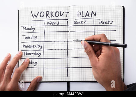 Elevated View Of A Person's Hand Filling Workout Plan In Checkered Notebook - Stock Photo