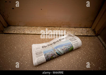A home delivery copy of the New York Times in front of an apartment door in New York on Thursday, February 8, 2018. - Stock Photo