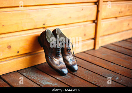 Brown leather man shoes near wooden wall. Man casual vintage accessories. - Stock Photo