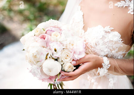 Bride holding wedding peony bouquet in your hands. White and pink flowers. Close-up