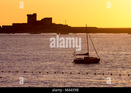 Sunset view of the Fort de Socoa in Saint-Jean-de-Luz, France, with a backlit boat in the foreground - Stock Photo
