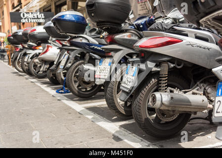 Rows of parked motorbikes and scooters in a street in the city of Bologna Italy - Stock Photo