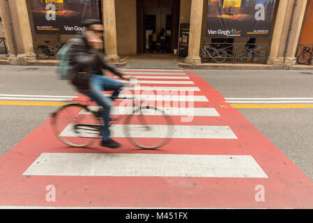 A red and white pedestrian crossing in a street in Bologna Italy  with a blurred cyclist with motion blur riding - Stock Photo