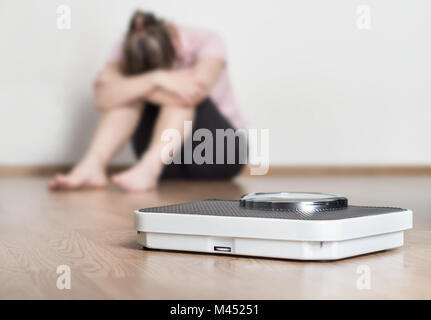 Weight loss fail concept. Scale and depressed, frustrated and sad woman sitting on floor holding head and arms on - Stock Photo