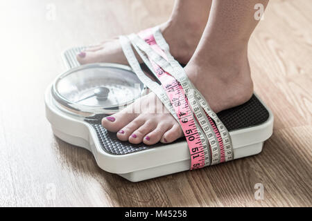 Anorexia and eating disorder concept. Feet tied up with measuring tape to a weight scale. Addiction and obsession - Stock Photo