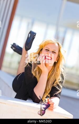 Young woman legs heels lying on her tummy stomach smiling loudly showing teeth - Stock Photo