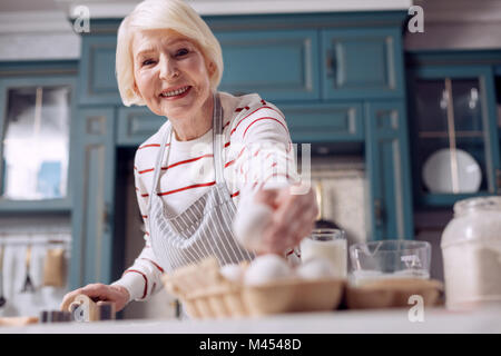 Pleasant elderly woman taking egg while making dough - Stock Photo