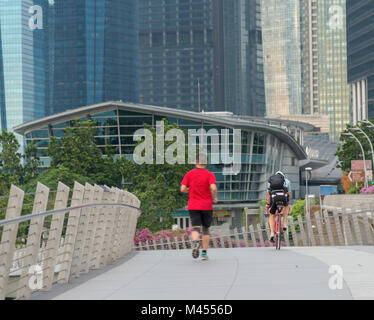 Runners and cyclists exercise in the morning along the bridge near Marina Bay in Singapore - Stock Photo