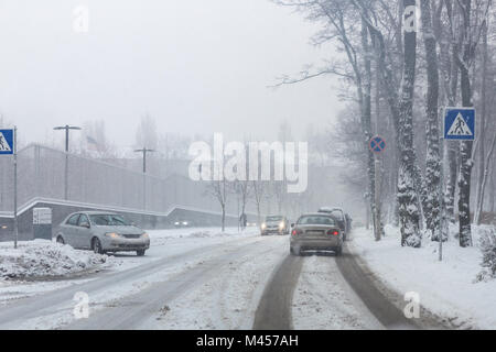 City street under snow during heavy blizzard in winter.  Poor snow removal. Shower   precipitation. Snowfall weather - Stock Photo