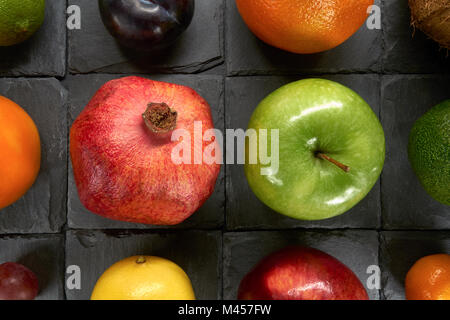 A variety of colorful fruits on squares of black shale - Stock Photo