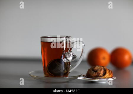 cup of strong black tea biscuit and two orange - Stock Photo