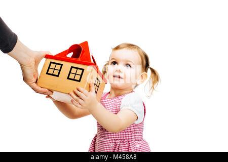toddler girl receiving a house - Stock Photo