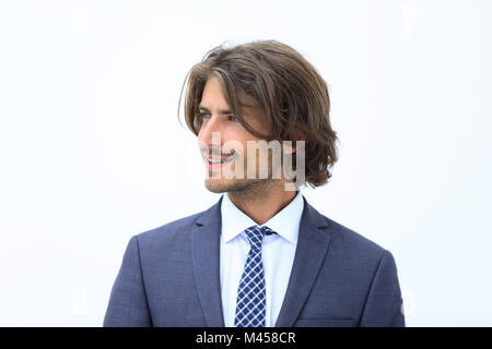 Handsome man in stylish clothes is looking away and smiling - Stock Photo