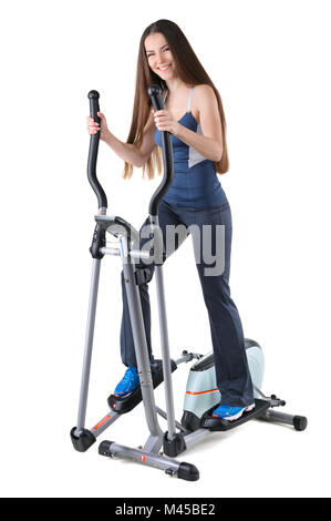 young woman doing exercises on elliptical trainer - Stock Photo