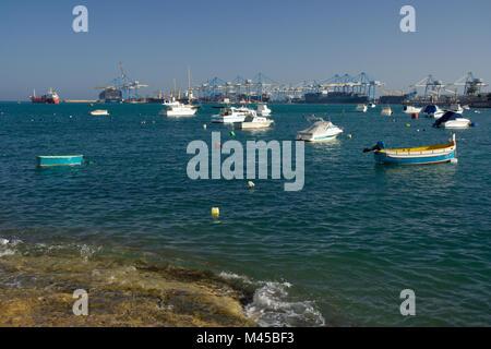 Small fishing boats near Birzebbuga, the big freeport in the background. - Stock Photo