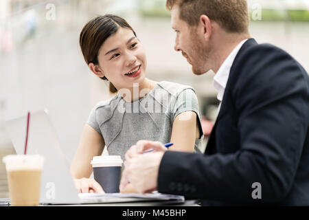 Young businessman and woman having discussion at sidewalk cafe - Stock Photo