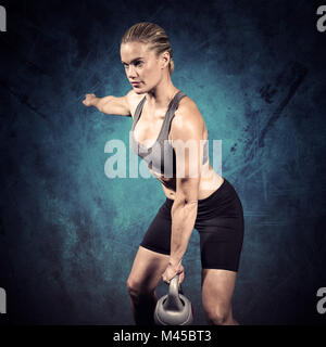 Composite image of muscular woman swinging heavy kettlebell - Stock Photo