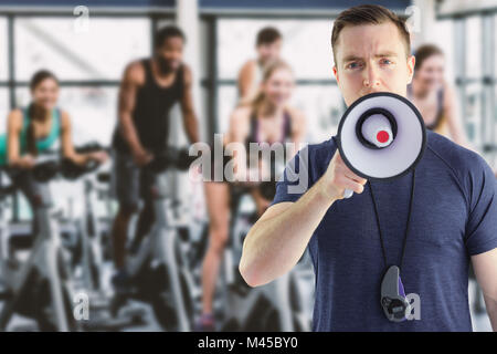 Composite image of male trainer yelling through the megaphone - Stock Photo