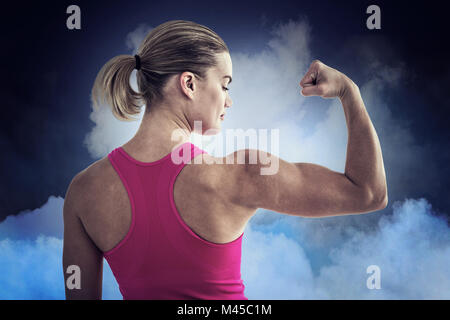 Composite image of rear view of muscular woman flexing muscles - Stock Photo