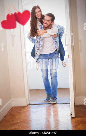 Composite image of young man giving girlfriend a piggyback ride - Stock Photo