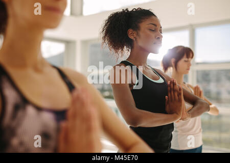 Fit young woman practice yoga with friends. Fitness female doing yoga meditation indoors in gym class. - Stock Photo