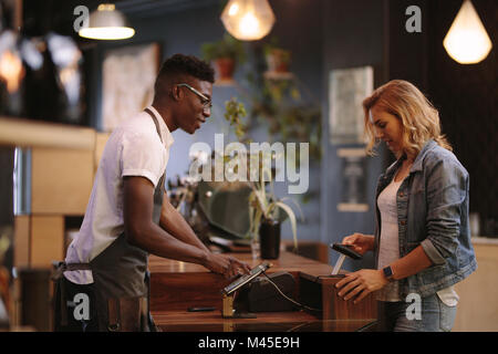 Coffee shop owner at the billing counter accepting payment from customer. Woman paying her coffee bills wirelessly - Stock Photo