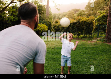 Father and son playing with a football in backyard garden. Happy little boy passing ball to his father. - Stock Photo