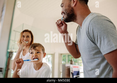 Cute little boy brushing teeth with his father and mother in bathroom. Young family brushing teeth together in bathroom. - Stock Photo