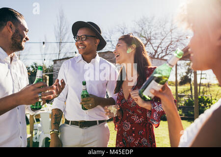 Happy young people having fun at the party and drinking beer. Group of friends hanging out together at a restaurant. - Stock Photo