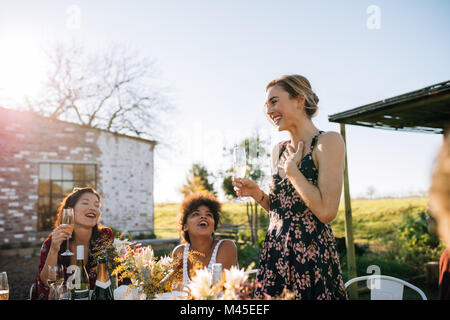 Overwhelmed woman sharing good news with friends at garden restaurant. Friends celebrating a special occasion at - Stock Photo