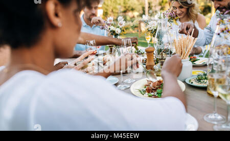 Group of friends enjoying meal at outdoor party. Men and women having lunch together at a restaurant. - Stock Photo