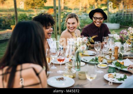Group of friends enjoying outdoor party in home garden. Millennials  enjoying summer meal at restaurant. - Stock Photo