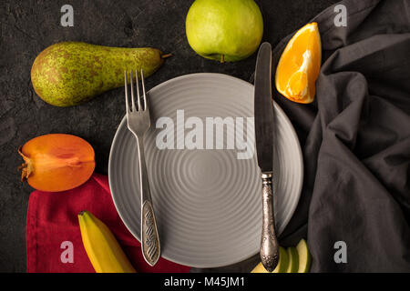 top view of empty plate with cutlery and fresh fruits on tabletop - Stock Photo