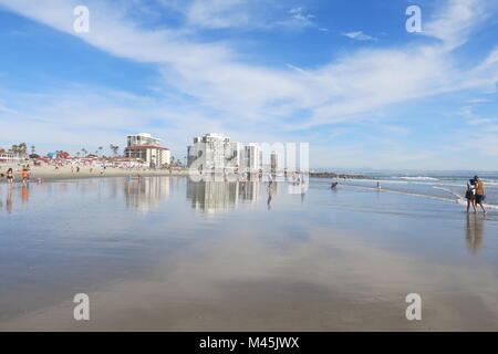 View of Coronado Beach on a sunny spring day, with the water reflecting a big sky - Stock Photo
