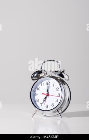 close-up view of shiny alarm clock on grey - Stock Photo